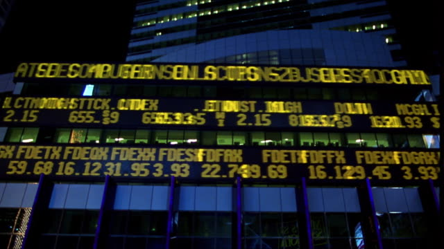 low angle time lapse digital stock ticker board on building exterior at night / nyc - trading board stock videos and b-roll footage