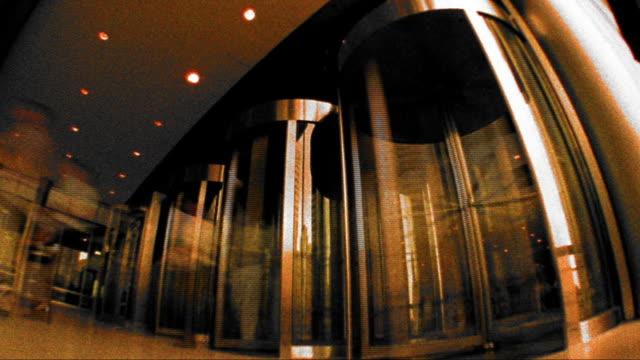 vidéos et rushes de grainy cross process low angle time lapse people entering + exiting through revolving doors - procédé croisé