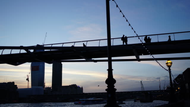 low angle time lapse shot of people walking across the millennium bridge, london. - stadtzentrum stock-videos und b-roll-filmmaterial