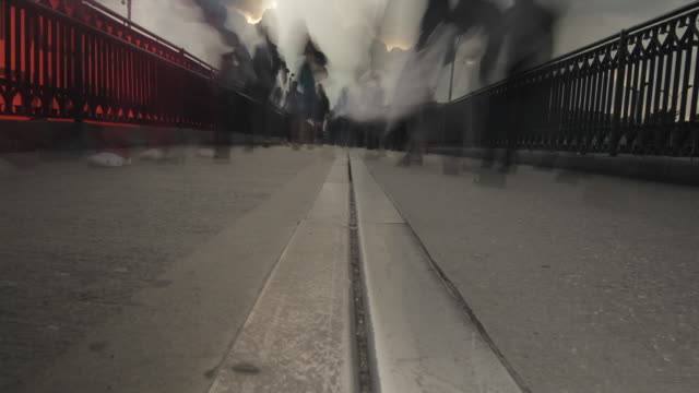 Low angle time lapse shot of people walking over a footbridge in the city of Bogota.