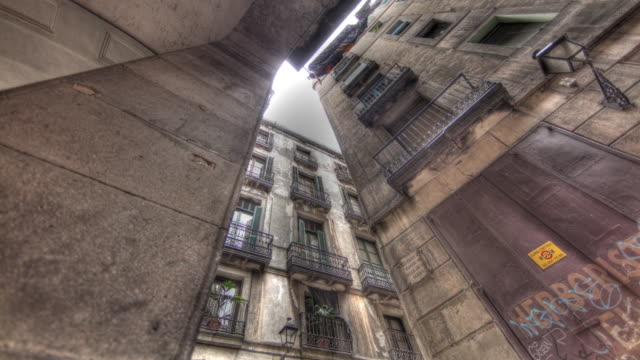 Low angle time lapse shot of raining falling on a narrow alleyway in a residential area of Barcelona.