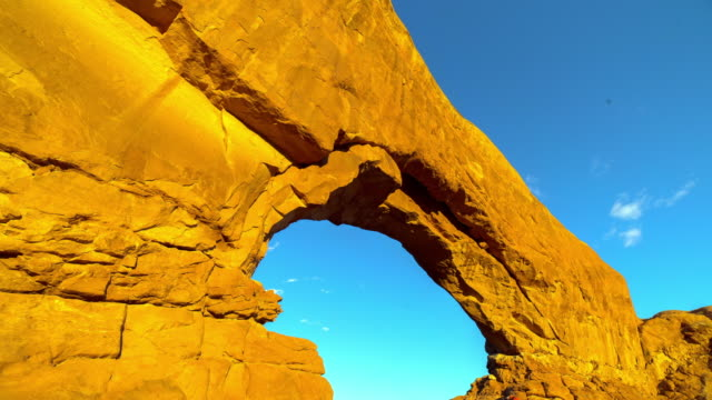 low angle time lapse shot of the windows section against blue sky during sunset - arches national park, utah - fast motion stock videos & royalty-free footage