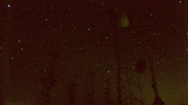 low angle time lapse starscape behind antenna towers at night