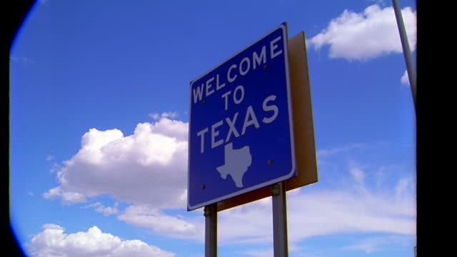 low angle MS time lapse 'WELCOME TO TEXAS' sign with clouds forming in background / Texas