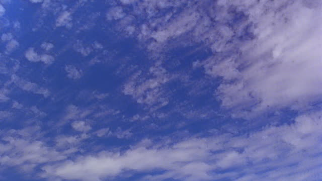 low angle time lapse white clouds moving fast across blue sky - 1985 stock-videos und b-roll-filmmaterial