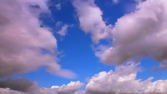 low angle time lapse white fluffy clouds moving across blue sky - 1 minute or greater stock videos & royalty-free footage