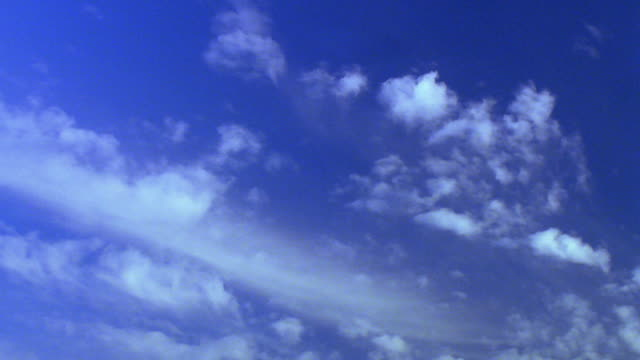 Low angle time lapse wispy clouds drifting slowly in blue sky / sky darkening