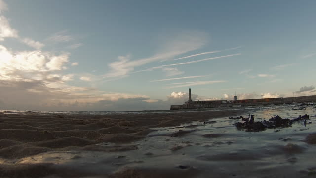 low angle time-lapse of tide coming in at sunset