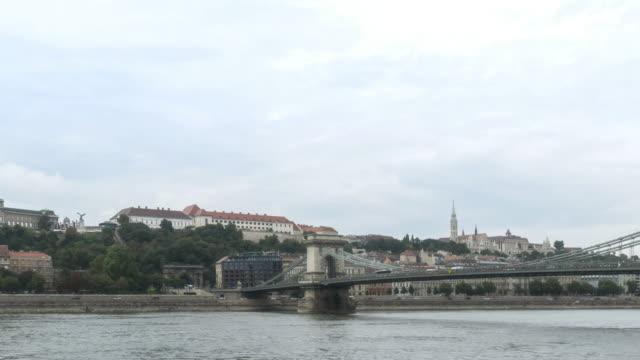 vídeos de stock, filmes e b-roll de baixo ângulo tl: vista da cidade ao redor do rio danúbio que consistia do palácio real e ponte da cadeia szechenyi em budapeste, hungria - chain bridge suspension bridge