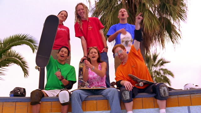overexposed low angle to high angle crane shot portrait young adults with skateboards sit on edge of pool, cheer + gesture - overexposed video stock e b–roll