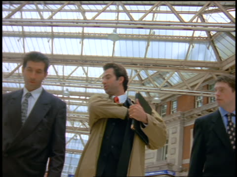 low angle tracking shot 3 businessmen walking in lobby of waterloo train station / london - shirt and tie stock videos & royalty-free footage