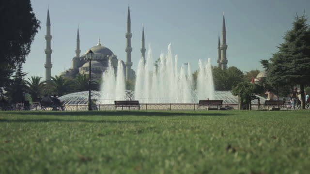 Low angle tracking shot across a fountain near the Sultan Ahmed Mosque in Istanbul.