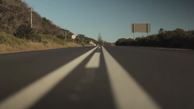 low angle tracking shot across a road on the outskirts of cape town. - surface level stock videos & royalty-free footage