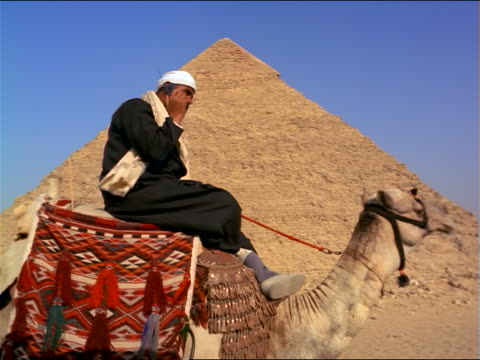 low angle tracking shot bedouin man riding camel + talking on cellular phone near pyramid / giza, egypt - westernisation stock videos & royalty-free footage