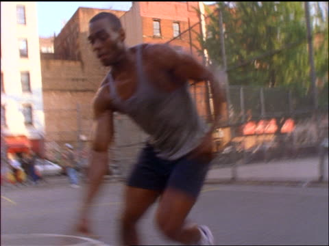 stockvideo's en b-roll-footage met low angle tracking shot black man dribbling basketball + missing dunk shot outside in nyc / hangs on rim - 1990
