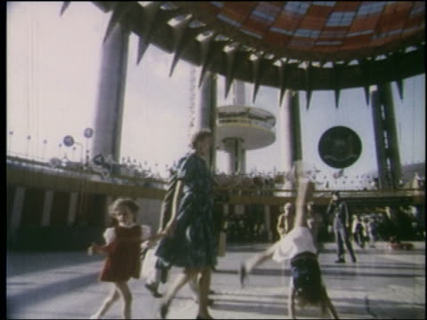 vídeos de stock e filmes b-roll de 1964 low angle tracking shot family walking in pavilion / girl does cartwheel / ny world's fair - 1964
