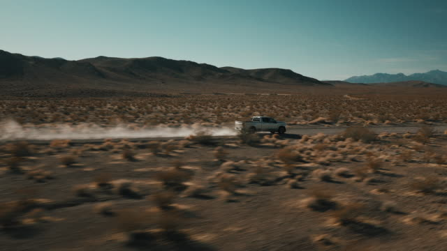 low angle tracking shot filmed by drone showing a truck crossing a dry dirt road, nevada, united states of america - ländliche straße stock-videos und b-roll-filmmaterial