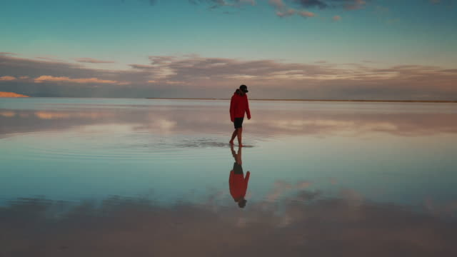 stockvideo's en b-roll-footage met low angle tracking shot filmed by drone showing the reflection of an adult male walking on the flooded bonneville salt flats at sunset, utah, united states of america - bonneville zoutvlakte