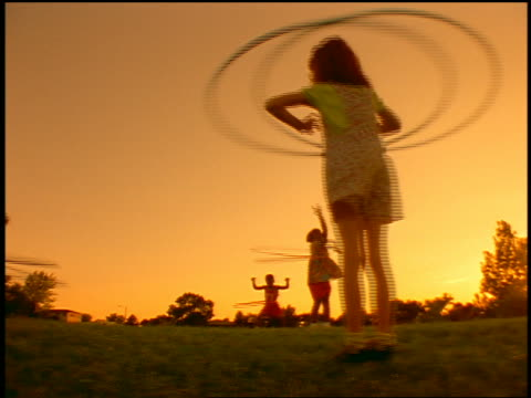 orange low angle tracking shot group of children using plastic hoops outdoors - plastic hoop stock videos & royalty-free footage