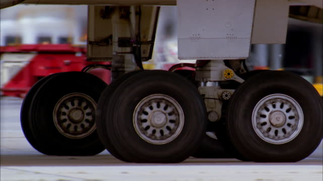 Low angle tracking shot jet landing gear / wheels rolling on runway