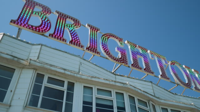 "low angle tracking shot moving over a ""brighton pier"" sign on brighton's palace pier. - brighton brighton and hove stock-videos und b-roll-filmmaterial"