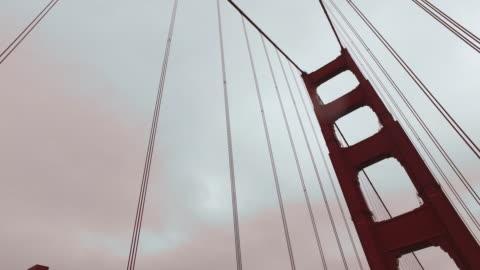 low angle tracking shot moving past the support cables and towers on the golden gate bridge. - hängbro bildbanksvideor och videomaterial från bakom kulisserna