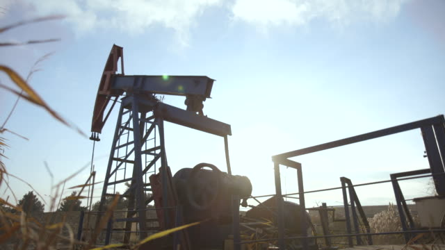 low angle tracking shot of a pumpjack in operation at an oil field near baku. - baku video stock e b–roll