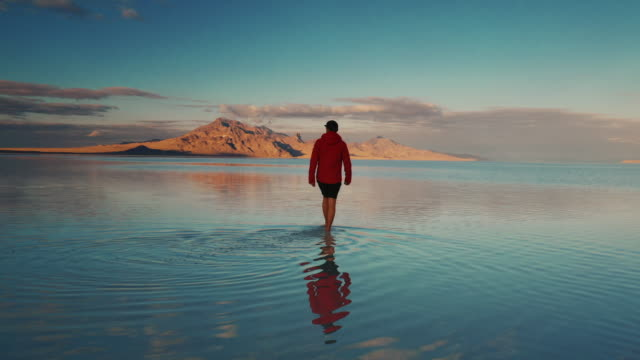 stockvideo's en b-roll-footage met low angle tracking shot showing a male walking towards a mountain on the flooded bonneville salt flats, utah, united states of america - bonneville zoutvlakte