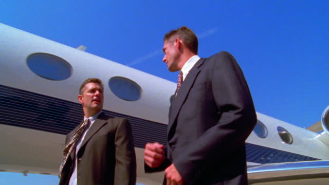 low angle MS tracking shot two businessmen talking + walking to steps to board airplane / one man answers cell phone