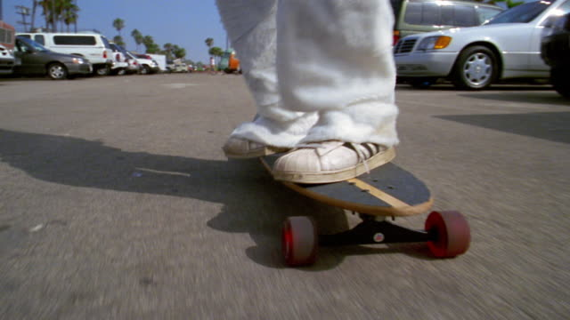 low angle tracking shot wide shot man in rabbit costume riding skateboard in parking lot / los angeles, ca - rabbit costume stock videos & royalty-free footage