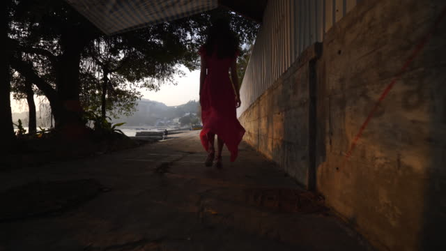 Low angle tracking shot, woman walks along coastline in China