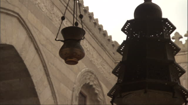 low angle, tracking-right - lamps hang in a courtyard ringed by carvings / egypt - electric lamp stock videos & royalty-free footage