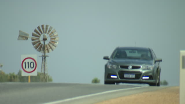 low angle traffic on highway moving over slight ridge in highway tin farm windmill on the side of the road beside a 110 km speed limit sign in the...