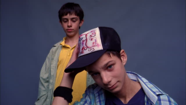 low angle two boys looking at cam / boy puts on baseball cap in foreground - baseball cap stock videos & royalty-free footage