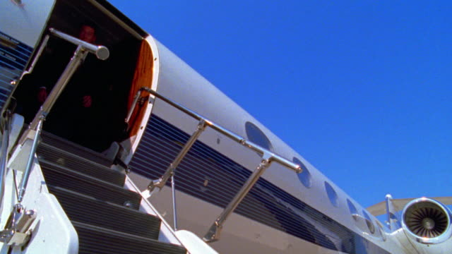 low angle ms two businessmen walking down steps de-boarding airplane - yuppie stock videos and b-roll footage