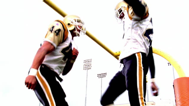 OVEREXPOSED low angle two football players dancing in celebration in end zone