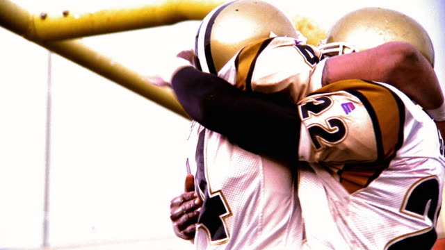 OVEREXPOSED low angle MS two football players hugging + dancing in celebration in end zone
