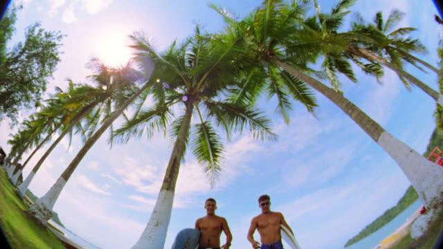 vídeos y material grabado en eventos de stock de fisheye low angle two men carrying surfboards walking toward + past camera high-fiving on beach - traje de baño de una pieza