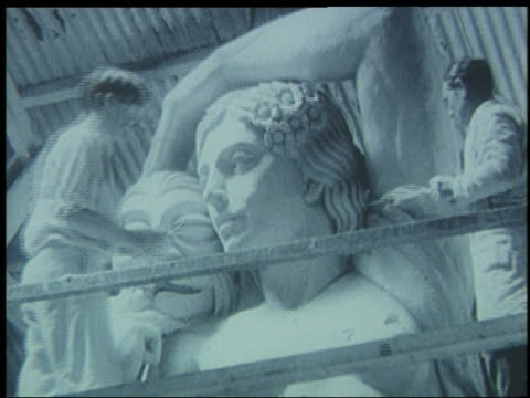 low angle two men working on large statue for world's fair - manipolazione di colore video stock e b–roll