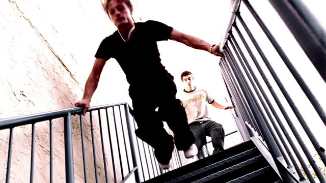 OVEREXPOSED low angle two teen boys running + jumping down metal stairs