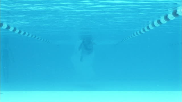 Low angle underwater view of swimmer doing front crawl towards camera
