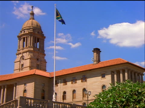 low angle union buildings with tower + south african flag waving / pretoria - establishing shot stock-videos und b-roll-filmmaterial