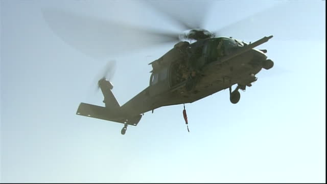 low angle, us army helicopter flies overhead in afghanistan - afghan national army stock videos & royalty-free footage
