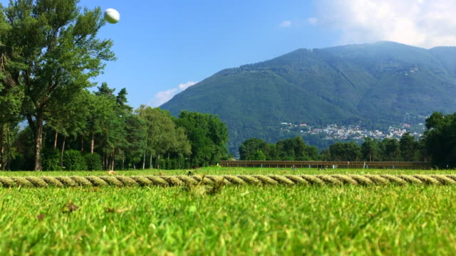 low angle view and zoom in on a golf ball been hitting with driver golf club on the driving range with mountain and trees in a sunny day in ascona,... - zoom in点の映像素材/bロール