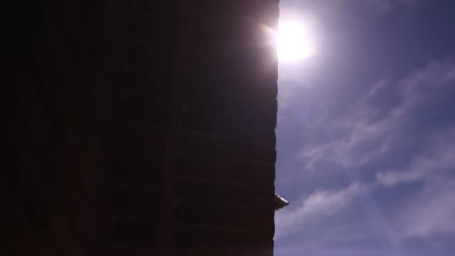vidéos et rushes de low angle view around wall of tower in madrid's famous bullring (plaza de toros de las ventas) to reveal the flag of the community of madrid on a flagpole - poteau d'appui