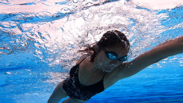 low angle view asian chinese female swimmer swimming across swimming pool - swimming goggles stock videos & royalty-free footage