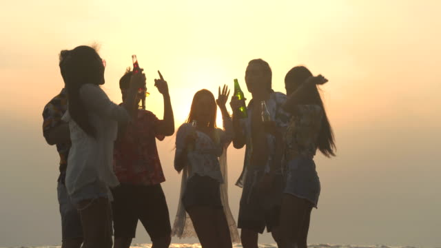 low angle view: beach party, group of young people silhouette celebrating in weekend - life events stock videos & royalty-free footage