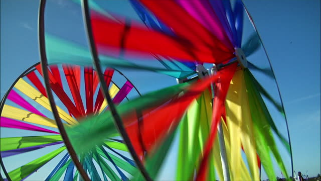vídeos de stock e filmes b-roll de low angle view. colorful pinwheels spinning in the wind. - moinho de papel