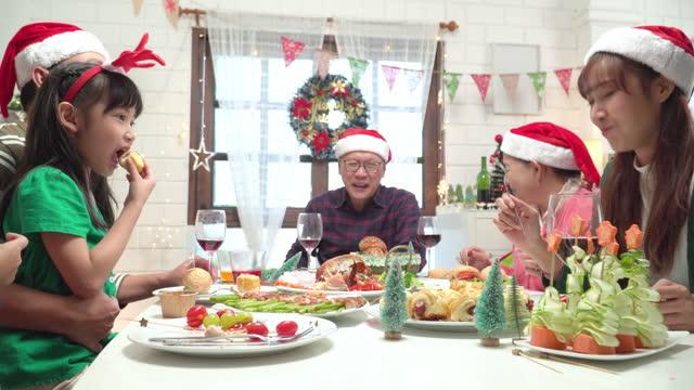 niedrige winkelansicht: tochter teilt brot, heiligabendessen mit mutter, südostasiatische mehrgenerationenfamilie, die um das abendessen für die weihnachtsfeier des dezemberfeiertags in einem mit weihnachtsbaum und ornament geschmückten haus sitzen. - 35 39 years stock-videos und b-roll-filmmaterial