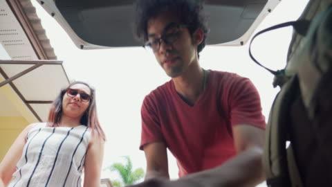 låg vinkel vy inifrån bilen: happy asiatiska par reser genom att köra bil och lastning hjul resväska bagage och backpacker från lyxhotell resort på semester sommar road trip på semester. livsstil av icke-kaukasiska resenären lastning bil. - lasta bildbanksvideor och videomaterial från bakom kulisserna
